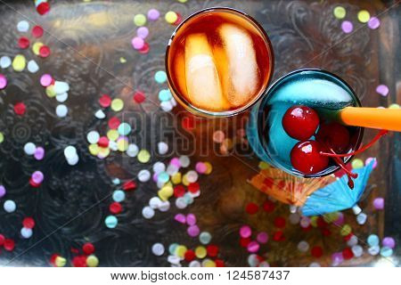 Over head view of bright and colorful cocktails on a silver platter with confetti. Room for copy/background