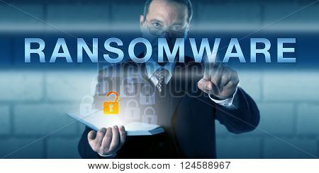 Security consultant is touching RANSOMWARE on a virtual interactive screen. Business metaphor and information technology concept for malware restricting system access for the victimized user.