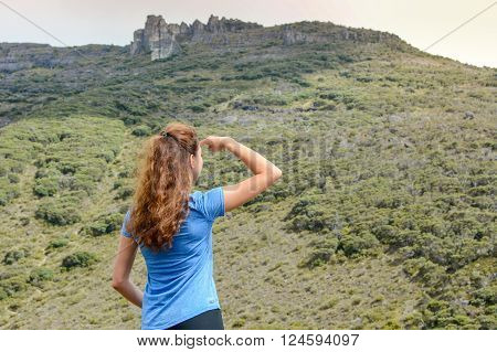 girl on a mountain looking at the distance with a hand blocking the sun poster