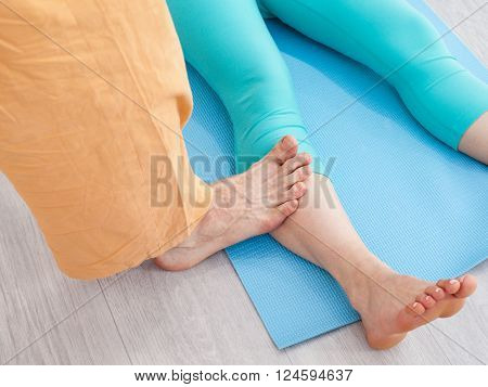 Thai massage session. Man presses on woman's leg by the foot