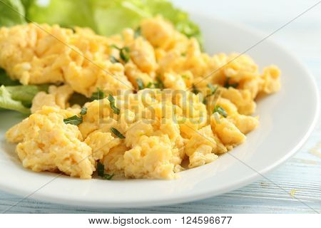 Scrambled eggs with vegetables on a blue wooden table poster