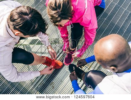 Multiethnic group of runners getting ready for a workout session - Athletes tying shoelaces and resting after a run outdoors
