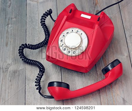 Red rotary telephone off hook on a wooden platform. Retro phone. The expectation of the subscriber.
