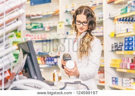 Pharmacist scanning price on a medicine box - Female doctor working in a pharmacy