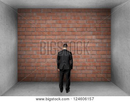 A businessman with bowed head stands in front of a brick wall in interior. Stalemate. Problem.