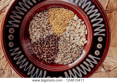 Collection Set of Cereal Grains: Millet Oat Corn Rice Buckwheat closeup shot on a wooden surfactant is in a plate