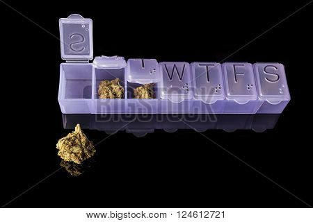 Marijuana buds in dosage plastic purple drugs container on black background from above