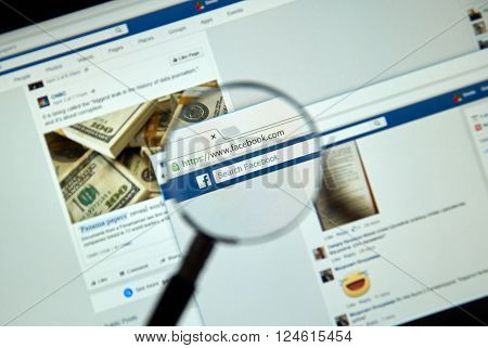 MONTREAL CANADA - MARCH 25 2016 - Facebook page under magnifying glass. Facebook is a corporation and online social networking service.