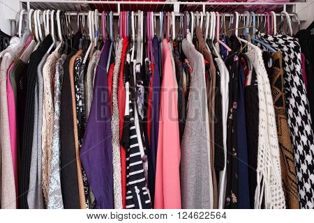 Crowded closet of colorful women's clothing on hangers