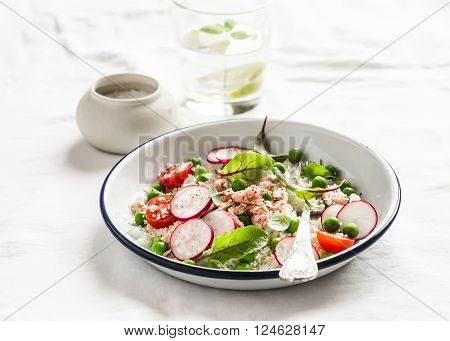 Delicious healthy food - salad with cous cous fresh vegetables and baked salmon. On a light background