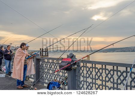 Istanbul Turkey - Jun 28 2015: A man wrapped in blanket was smoking and fishing on Galata Bridge with other people during daybreak time facing Bosphorus Strait.