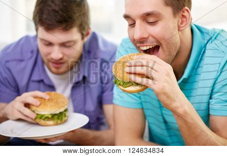 fast food, unhealthy eating, people and junk-food - close up of happy friends eating hamburgers at home