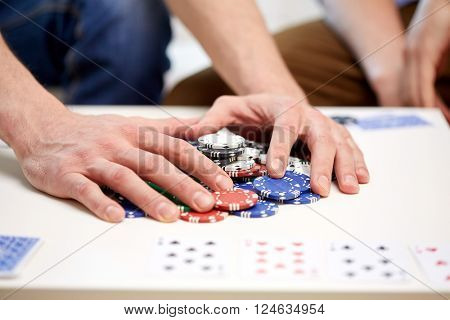 leisure, games, gambling and entertainment - close up of male hands with casino chips and playing cards making bet or taking win at home