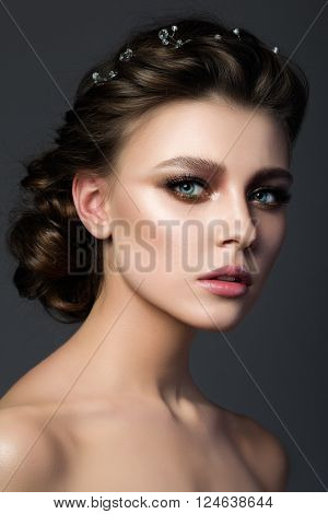 Portrait of young beautiful woman with bridal makeup and coiffure. Modern smokey eyes make up. Studio shot. Salon make-up