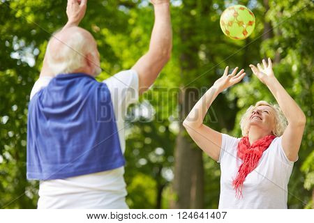 Old man and senior woman playing with a ball in a park
