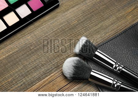 Eyeshadow Palette and Two Powder Or Blush and Foundation Makeup Brushes Laying On Cosmetic Bag on Brown Wooden Background Close-up With Empty Space
