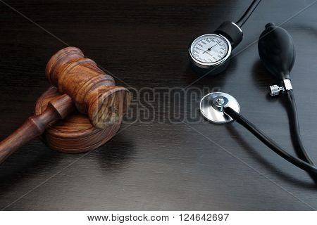 Judges Gavel And Medical Equipment On Black Wooden Background