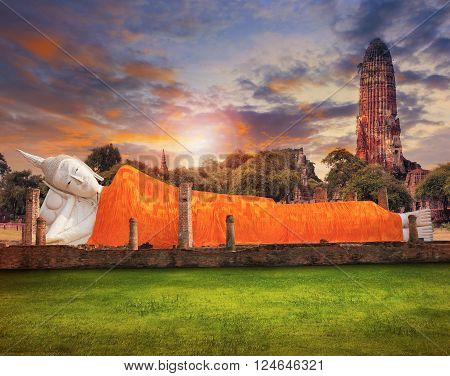 sleeping buddha statue and ancient brick pagoda against beautiful sun set sky with copy space use for beautiful asia scenic and religious background