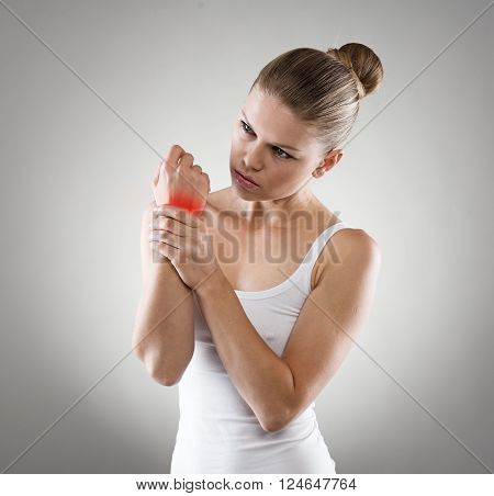 Portrait of young Caucasian woman exercising her painful wrist. Chronic osteoarthritis or joint rheumatism. Medical treatment and health care concept.