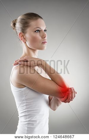Joint inflammation indicated with red spot on female's elbow. Arm pain and injury concept. poster