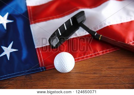 Golf ball, club and American flag on wooden table. Popular sport concept