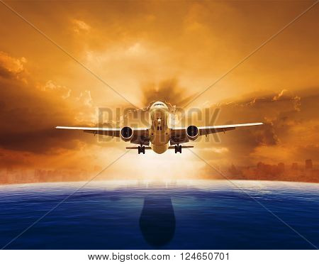 passenger jet plane flying over beautiful sea level with sun set sky above and urban skyline behind