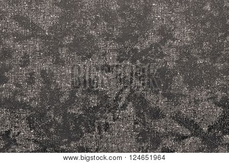 texture of textile fabric with spots from glossy scaly leather of dark beige color for an abstract background or for the textured wallpaper