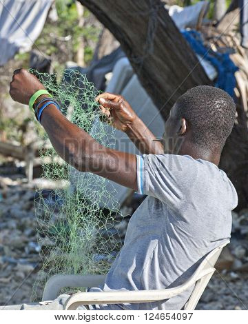 SAINTARD, HAITI -  FEBRUARY 29, 2016: The back of an unidentified Haitian fisherman inspecting a nylon fishing net that he's been mending near Saintard, Haiti on Feb. 29. 2016.