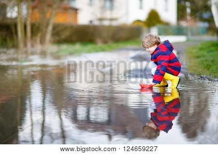 Funny little kid boy in rain boots playing with paper boat by a puddle on warm spring day. Active leisure for children. Child having fun outdoors.