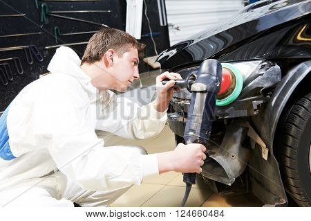 mechanic repairing and polishing car headlight