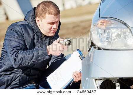 Insurance agent photographing car damage for claim form poster