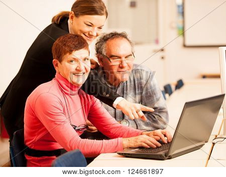 Young woman teaching elderly couple of computer skills. Inter generational transfer of knowledge.