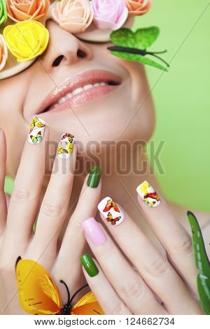 Multicolored manicure with pictures of butterflies on the nails and decorative rosettes on the eyes of a young woman.