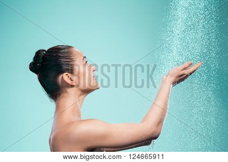 Woman enjoying the water in the shower under a water jet on blue background