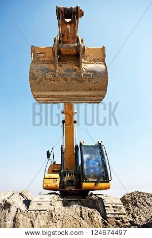 Excavator loader machine during earthmoving works outdoors at construction site