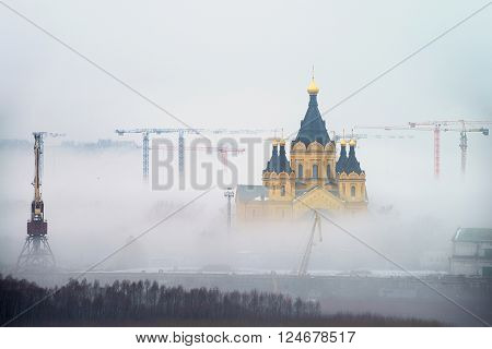 Cathedral of St. Alexander Nevskiy in Nizhny Novgorod Russia covered with fog. Numerous construction cranes
