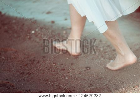 Young woman in white dress walking alone on the beach blured photo in vintage retro style blured