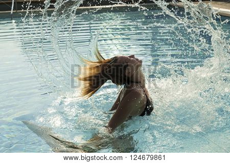 Beautiful blond girl having fun in a swimming pool swaying her hair from the water making a water splash