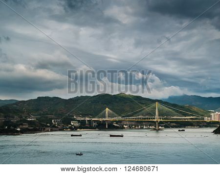 Picturesque landscape with a view on Tsing Ma Bridge, Hong Kong, China. A view with urban and industrial merging with natural mountaings on islands and gorgeous clouds.