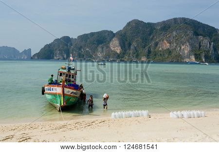 PHI PHI DON, THAILAND - MARCH 2: Wooden boat with drinking water sellers landed on the sandy beach of tropical island on March 2, 2015. Tropical Ko Phi Phi National Park covers about 39000 hectares