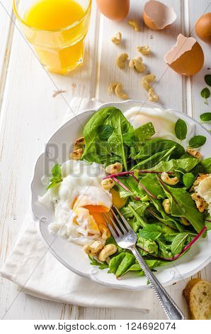 Lamb lettuce salad with fried egg fresh orange juice and roasted nuts and baquette