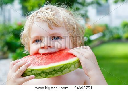 Funny little toddler boy with blond hairs eating watermelon in summer garden. Kid tasting healthy snack. Healthy food for children.