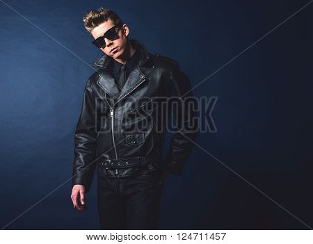 Macho retro 50s fashion man wearing shades and leather jacket.