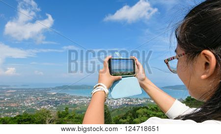 Young women tourist take photos high angle view of Ao Chalong bay and city sea side with mobile phones on top of Yot Khao Nak Kerd Hill in Phuket Province Thailand 16:9 wide screen poster