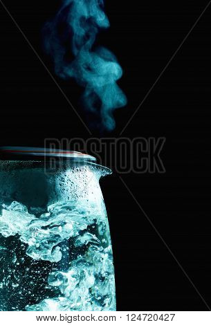 glass electric kettle with boiling water, black background