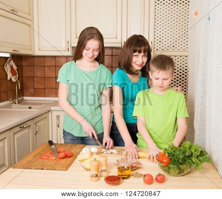 Happy family cooking pizza in the kitchen. Teenager boy and girl with their mother making pizza at home.