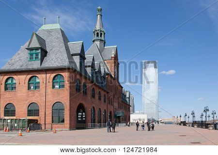 JERSEY CITY NEW JERSEY - MARCH 6: People enjoy the day at Liberty State Park on March 6 2016. The old CNJRR building and Goldman Sachs tower are seen.
