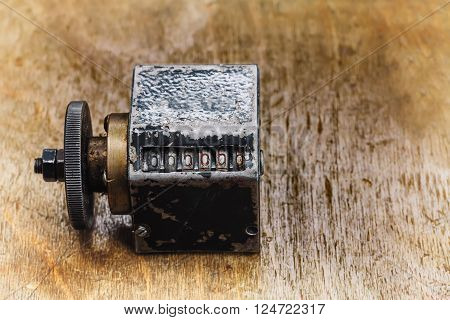 Vintage cliche stamp with number 666666. aged metal counter mechanism on wooden textured table. Calculation concept. macro view, shallow depth of field