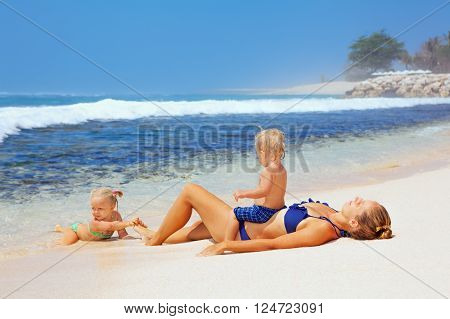 Happy family - mother baby son and daughter lying on sand beach and look at sea surf after swimming in clear water. Active parents and people outdoor activity on tropical summer vacations with child