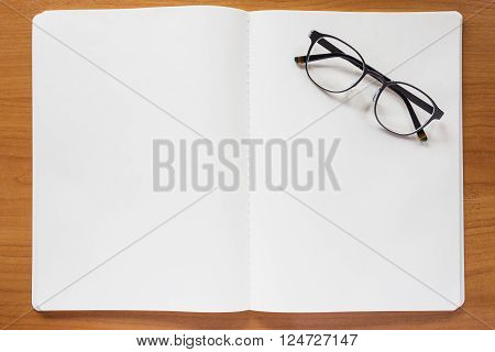 Bland note book with eyeglasses on top of wood table